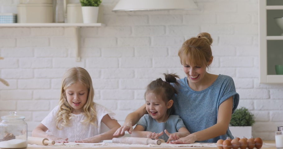 Cute funny children daughters and mother having fun cooking play with flour in kitchen, happy mum teach kids siblings help prepare dough for cookie with rolling pin together learn bake pastry at home