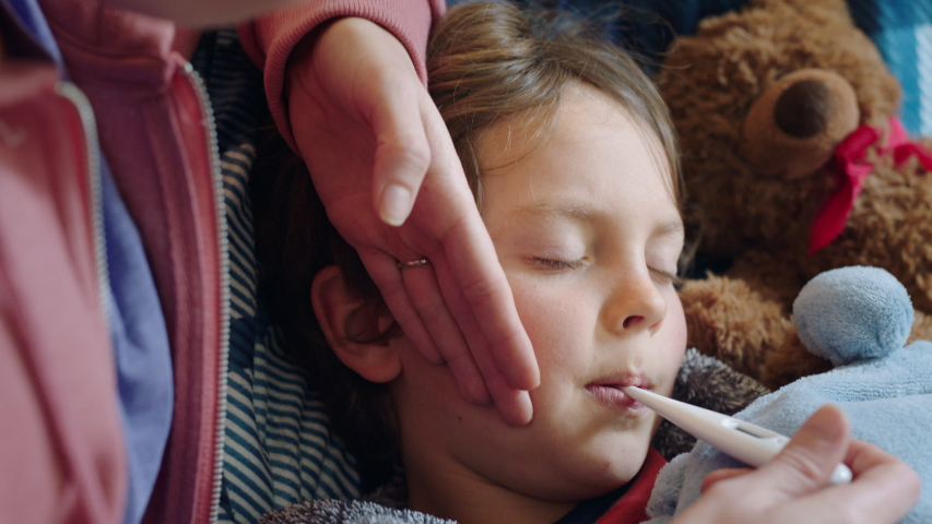 Mother caring for sick child lying in bed with flu measuring temperature using thermometer little girl at home with fever mom giving health care | Shutterstock HD Video #1034147054