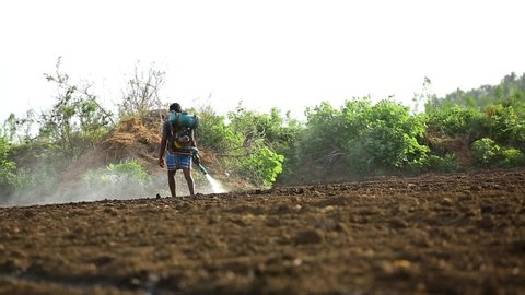 Madurai,tamil nadu,india- july 28,2019: farmer spraying preparing in  farmlands agricultural work in processing chemical to soil, cultivation of  land the city of madurai in southern india