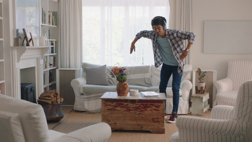 Happy young man dancing at home celebrating success listening to music wearing headphones having fun dance in living room on weekend | Shutterstock HD Video #1034230154