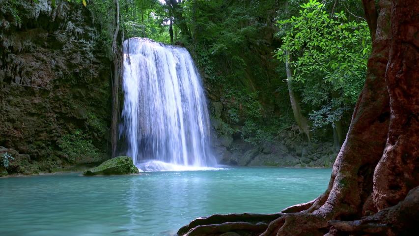 Rushing water of turquoise Erawan cascade waterfall. Kanchanaburi National Park, Thailand. Tropical fantasy. Exotic plants. Lush vegetation. Beauty of nature in wild jungle. Wonderful asian flora