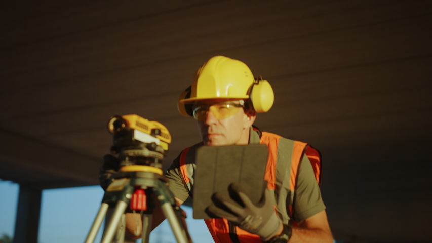 Inside of the Commercial / Industrial Building Construction Site: Professional Engineer Surveyor Takes Measures with Theodolite, Using Digital Tablet Computer