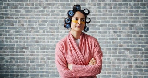 Angry girl with hair curlers and eye patches standing with arms crossed alone on brick wall background rolling eyes and shaking head. Emotions and people concept.
