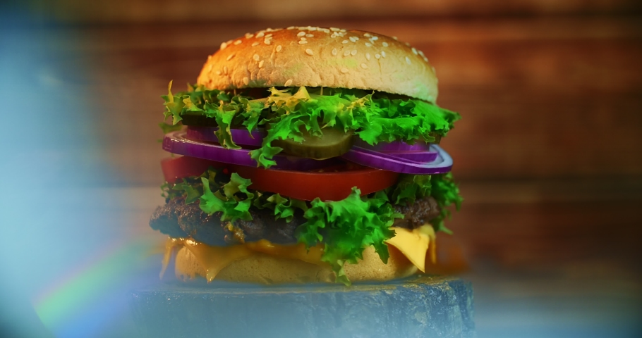 A big tasty burger with meat patty, onions, vegetables, melted cheese, lettuce and mayonnaise sauce. Isolated hamburger rotates on a dark wooden background. | Shutterstock HD Video #1034336024