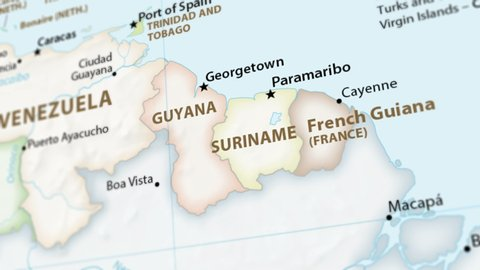 Guyana, Suriname and French Guiana on a political map of the world. Video defocuses showing and hiding the map (4K UHD).