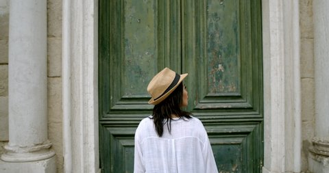Traveller in fedora sightseeing and walking towards massive antique door in the historic city of Venice Italy