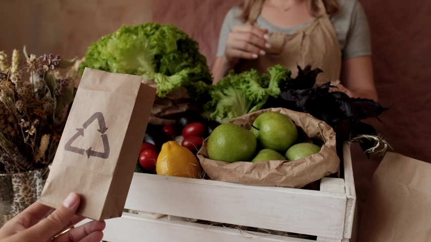 Recyclable Paper bag in vegetable shop.   Woman seller putting food into eco-friendly paper bags. Eco shopping, consumption, zero waste, no plastic  | Shutterstock HD Video #1034480264