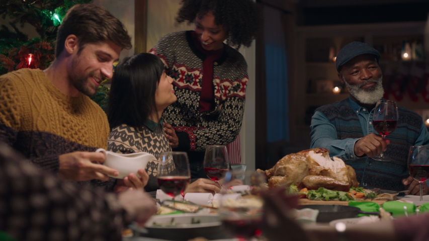 Happy couple enjoying christmas dinner with friends celebrating festive holiday with family sharing evening meal at home 4k | Shutterstock HD Video #1034494424