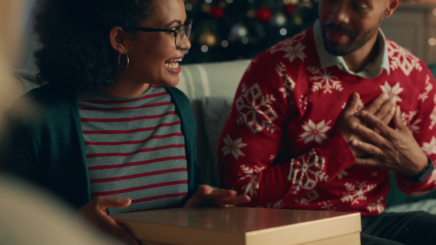 Christmas gift woman opening present with surprise sexy underwear laughing enjoying funny joke with friends and family celebrating festive holiday at home 4k | Shutterstock HD Video #1034495504