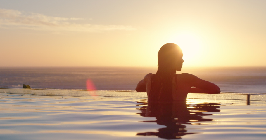 Woman relaxing in swimming pool at luxury hotel spa enjoying beautiful sunset view of ocean mediterranean travel holiday resort 4k