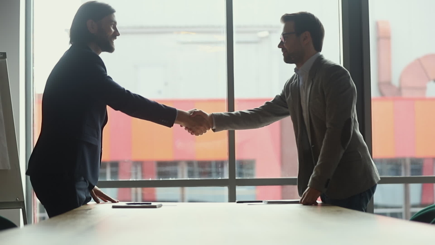 Two businessmen negotiators wear suits shake hands after successful negotiations, seller banker handshake partner client investor make investment partnership deal agreement trust concept, side view | Shutterstock HD Video #1034587604