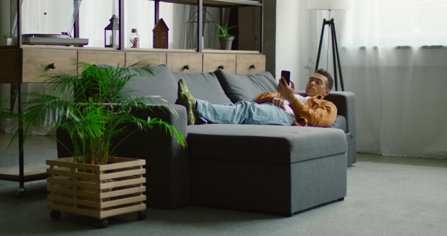 Handsome young Hispanic man is lying on sofa, using his smartphone, gadget, browsing, relaxing, enjoying weekend in studio apartment. Slow motion, 4K. Shot on RED camera. | Shutterstock HD Video #1034642324