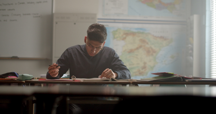 Young student studying and taking notes in classroom surrounded by warm daylight | Shutterstock HD Video #1034649794