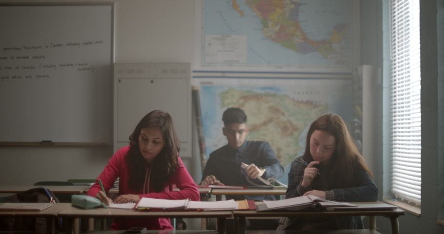 Group of young students in class reading, taking notes and doing their homework | Shutterstock HD Video #1034649854