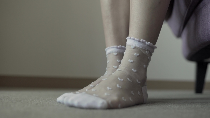 4k side view of girl putting on and taking off fashionable lavender heart pattern mesh socks | Shutterstock HD Video #1034656424