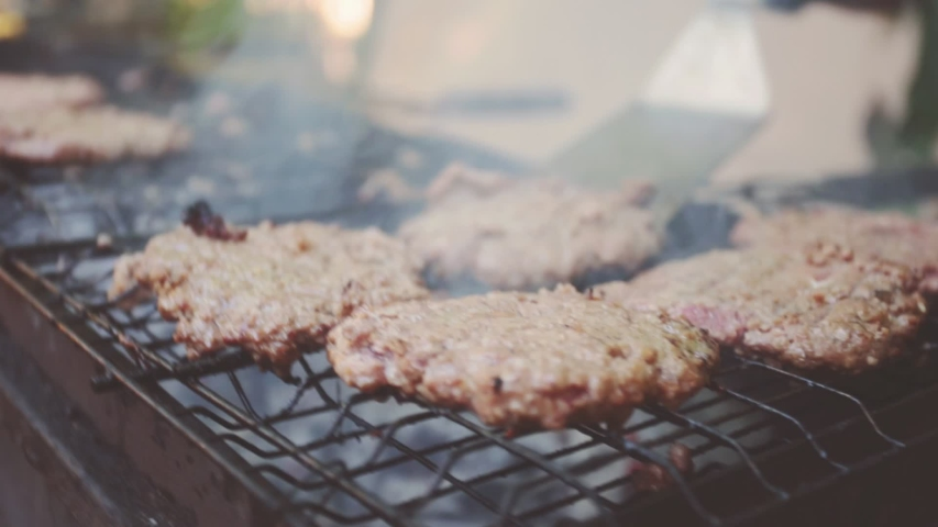 Street food festival. chef cooks delicious burgers. Low-depth of field, warm color grading | Shutterstock HD Video #1034663324