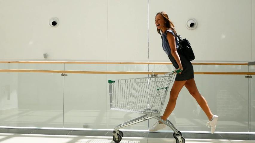 Beautiful young girl having fun riding on shopping cart at supermarket.
