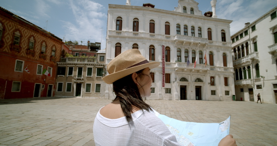 Female traveller looking up at street signs and map trying to find her way wearing fedora travelling abroad standing in Italian square in Venice Italy | Shutterstock HD Video #1034717864