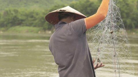 Luang Prabang / Laos - 08 10 2015: Adult male wearing bamboo coolie hat untangling fishing net on boat by river in Luang Prabang, Laos