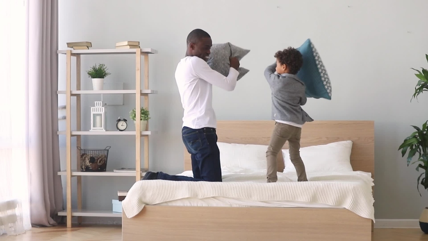 African father enjoying pillow fight with little mixed race son on bed at home, carefree funny older younger brothers spend free time on weekend together play active game holding cushions having fun #1034756084
