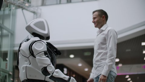 Interaction of man and modern technologies of artificial intelligence. Close up male hand of scientist shakes robotic arm. Robotic and human hands join in a handshake. Meeting and greeting friends