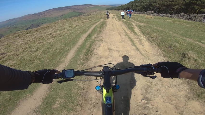 Peak District National Park / United Kingdom (UK) - 04 20 2019: POV cyclist on E Mountain Bike cycling on dirt trail riding past walkers in the Peak District, UK during Easter Weekend, April 2019
