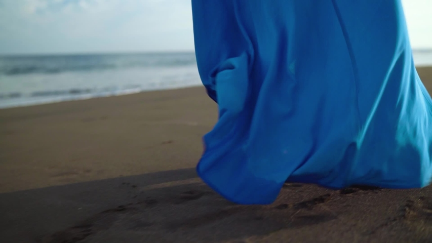 Woman in beautiful blue dress walking along a black volcanic beach. Slow motion