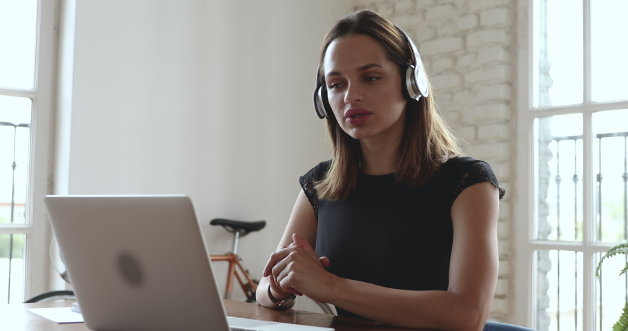 Smiling young business woman receptionist wear wireless headphone video conference calling on laptop computer talk by webcam in online chat, customer support service and online study teaching concept | Shutterstock HD Video #1035023864