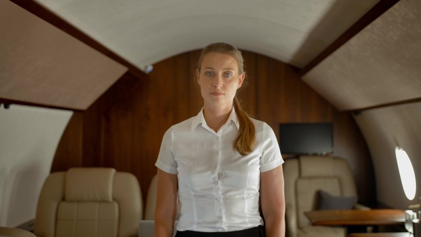 Portrait of confident rich business lady inside of her own luxury private business jet smiling and looking at camera. Rich person concept. 4k UHD. | Shutterstock HD Video #1035081674