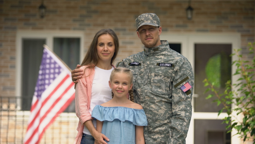 Happy american patriots family looking at camera, social insurance for veterans