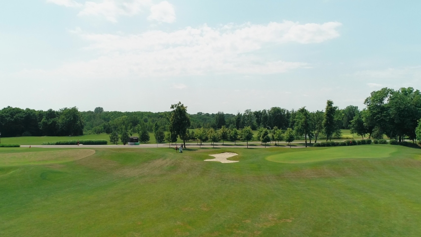 Aerial view of a green golf course with beautiful trees and forest, blue sky with clouds on sunny day in the summer time. 4K drone footage.   Shutterstock HD Video #1035175844
