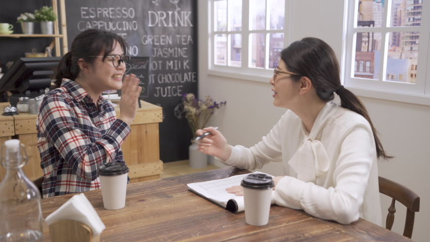 Two asian women laughing during job interview cafe bar. young girl new fresh graduate talk about funny experience to interviewer. lady tester holding pen reading resume on wooden table in coffee shop | Shutterstock HD Video #1035209294