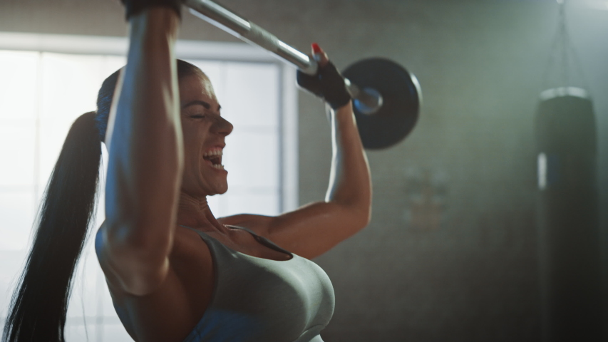 Athletic Beautiful Woman Does Overhead Lift with a Barbell in the Gym. Gorgeous Female Professional Bodybuilder Does Weight Lift Workout Exercises in the Hardcore Training Facility. Zoom in | Shutterstock HD Video #1035217664