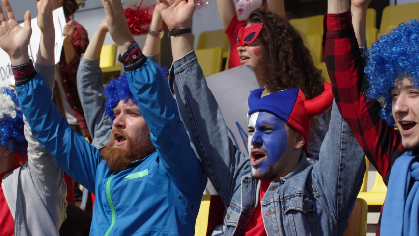 Medium panning shot of loyal male football club fans standing on stadium tribune, clapping hands raised above head, and chanting slogans in unison, and girlfriends with pompoms and banners behind