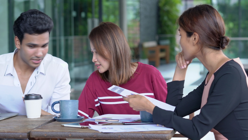 4K Medium dolly shot of young adult asian businessman and businesswoman freelance discussion business together at coffee shop outdoor. Teamwork young businessman and businesswoman working together #1035265424