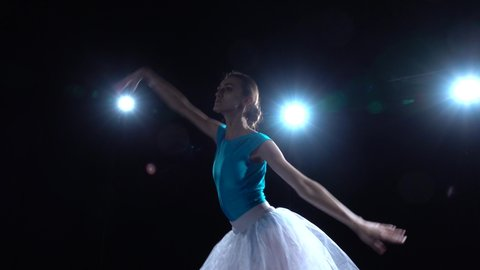 Gracefully thin professional ballerina in blue sport swimsuit and white tutu is spinning around and performing classical ballet in twilight against a spotlights on black studio background. Close up.