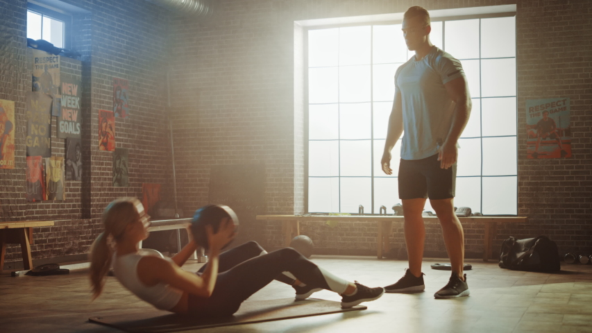 Beautiful Young Girl Exercises with Personal Trainer, Doing Sit-ups with Medicine Ball, Throwing Pass Back and Forth. Fit and Strong Couple Workout. Exercising Strength, Cardio and Power | Shutterstock HD Video #1035271484