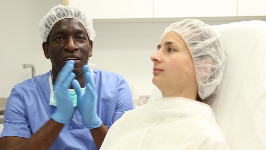 Cosmetician male in mask  before aesthetic facial injection, woman in amchair in medical  office  | Shutterstock HD Video #1035274334
