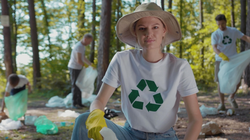 Close up young woman with hat cleans forest of debris folding it in plastic bag look at camera smile  | Shutterstock HD Video #1035318224