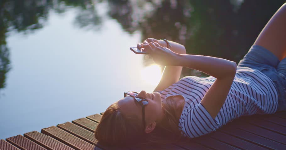 Woman using smartphone outdoors, smiling and relaxing on a wooden jetty near the lake with sunny backlit background, lens flare.