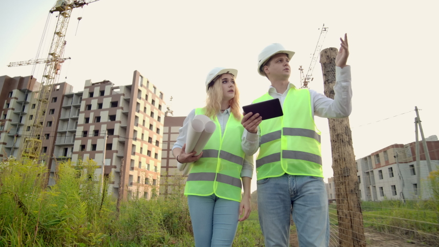 Business, building, industry, technology and people concept - smiling builder in hardhat with tablet pc computer along with woman with drawings of builders at construction site. | Shutterstock HD Video #1035355364