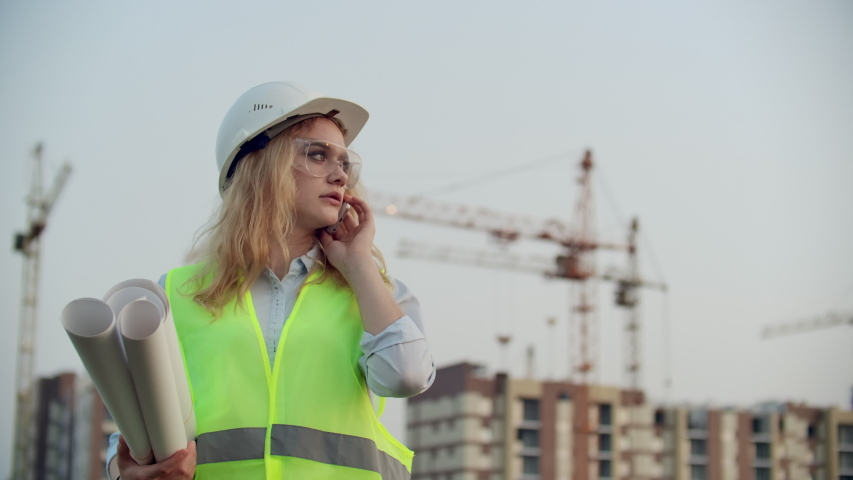 Portrait of a woman engineer in a helmet talking on the phone on the background of construction with cranes holding drawings in his hands. Female engineer on construction site | Shutterstock HD Video #1035360344