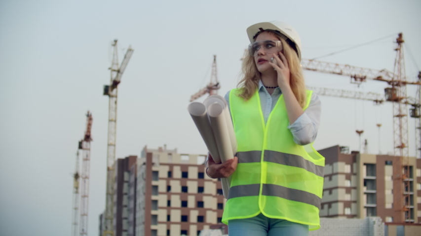 Woman Builder talking on the phone with the contractor with drawings in his hands on the background of buildings under construction and cranes. | Shutterstock HD Video #1035360374