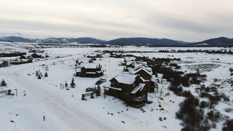 Aerial Forward: A Beautiful Snow Covered Neighborhood of Wooden Cottages in Colorado with a View of the Distant Rockies