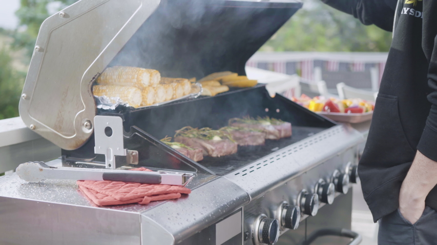 Grilling New York steak with a slice of butter and rosemary on an outdoor gas grill.   Shutterstock HD Video #1035395054