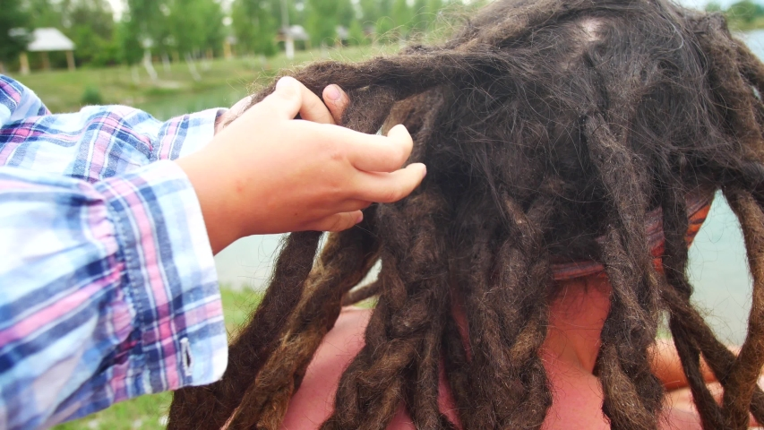 Childs weave braids to his dad from his dreadlocks. | Shutterstock HD Video #1035440024