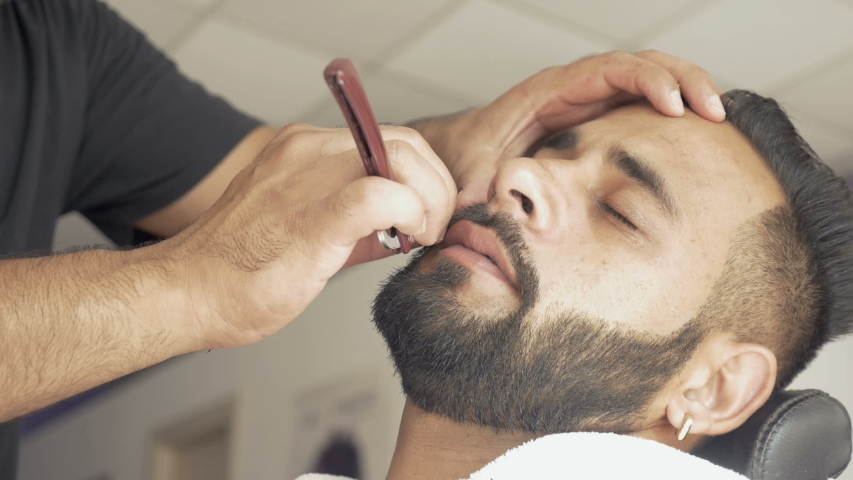 Handsome young man getting his beard shaved at barbershop. Beard cut with a straight razor in close-up. Professional barber shaves customer beard in a salon with an old-fashioned straight razor. | Shutterstock HD Video #1035516794