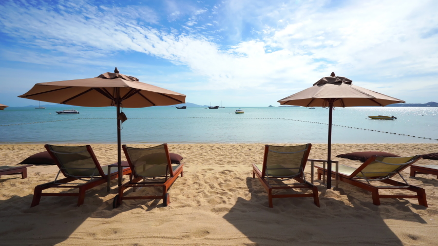 Sun recliners shaded by beach umbrellas lookout on the ocean horizon filled with pleasure boats, yachts, and ferries under a bright blue sky | Shutterstock HD Video #1035517754