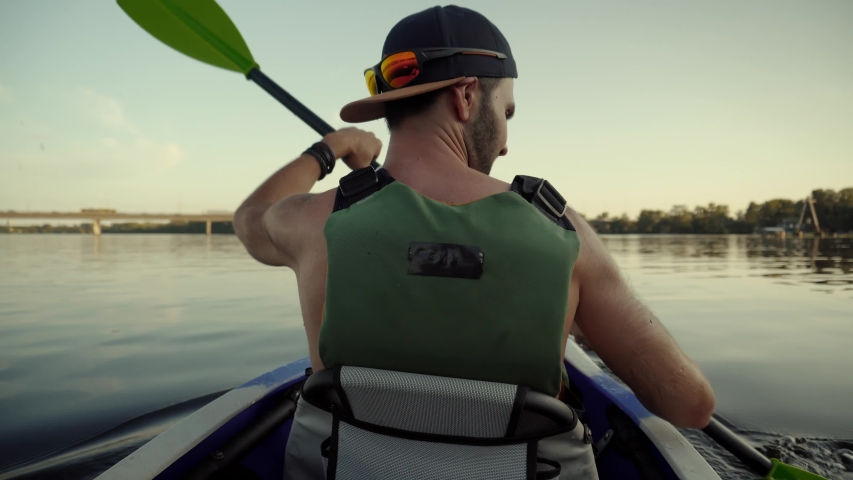 Man Floating On Pond In Boat And Enjoying Views.Male In Life Vest Swimmimg On Canoe.Strong Man Swim On Kayak Boat On River.Tourist Explores Beautiful River In Kayak Boat At Sunset.Travel Water Tourism | Shutterstock HD Video #1035518864