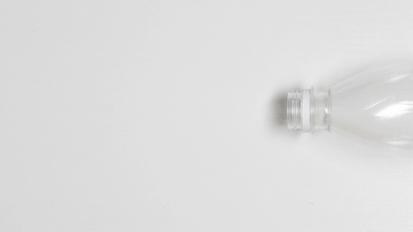 Crumpled plastic bottle moving on white background, environment pollution | Shutterstock HD Video #1035543644